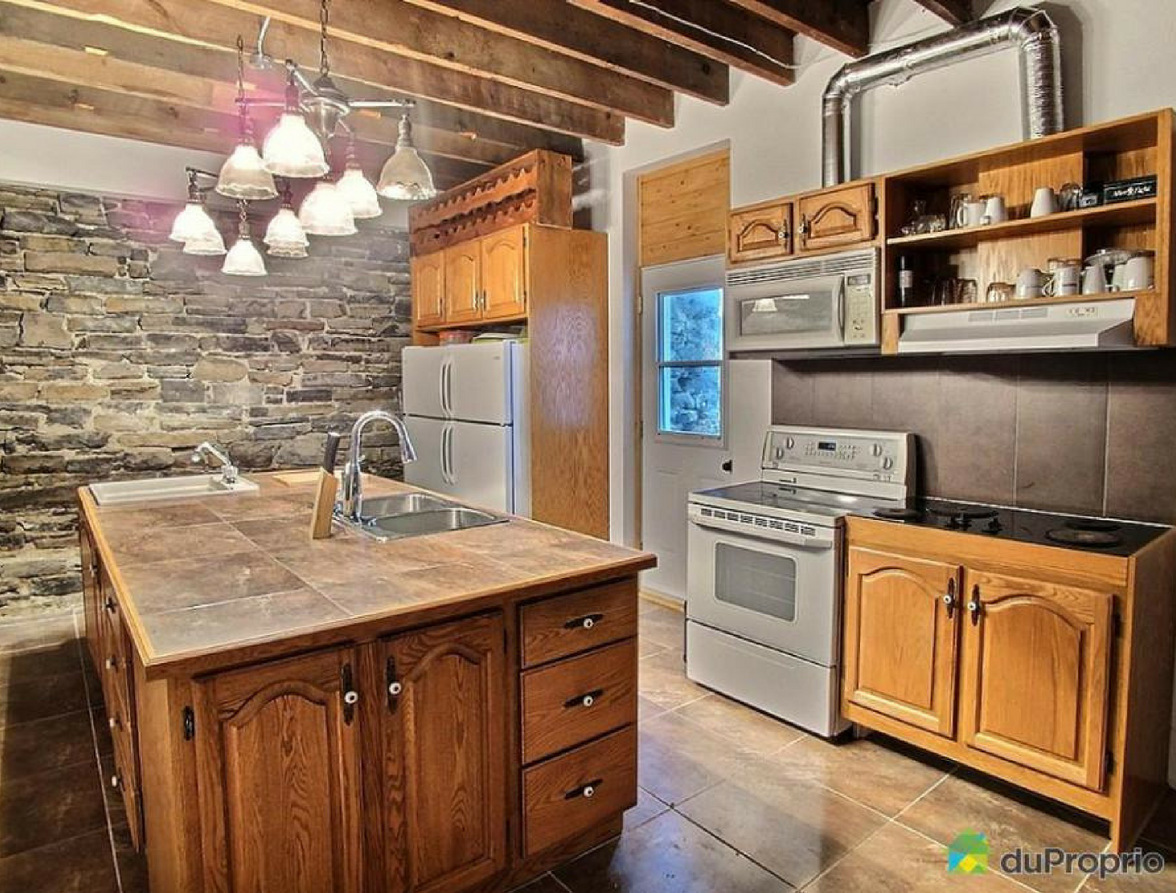 A photograph of the kitchen in which you see the sink, stove, fridge etc...